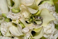 Wedding rings in flowers stock image