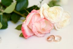 Wedding rings on flowers background stock photography