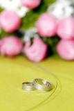 Wedding Rings with flowers on background Royalty Free Stock Image