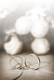 Wedding Rings with flowers on background. Closeup on wedding Rings with flowers on background in sephia coloring Stock Image
