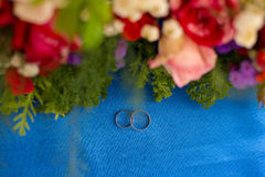 Wedding rings and flowers. Wedding rings in an environment of flowers on blue fabric Stock Photography