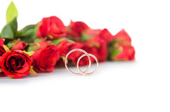 The wedding rings and flowers isolated on white background Royalty Free Stock Photos