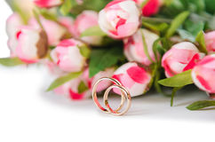 The wedding rings and flowers isolated on white background. Wedding rings and flowers isolated on white background Royalty Free Stock Photo