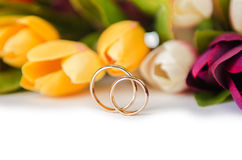 The wedding rings and flowers isolated on white background. Wedding rings and flowers isolated on white background Royalty Free Stock Photography
