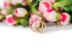 The wedding rings and flowers isolated on white background. Wedding rings and flowers isolated on white background Stock Photo