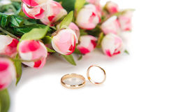 The wedding rings and flowers isolated on white background. Wedding rings and flowers isolated on white background Royalty Free Stock Image