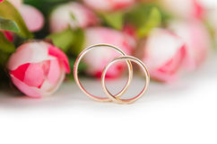 The wedding rings and flowers isolated on white background. Wedding rings and flowers isolated on white background Stock Photography