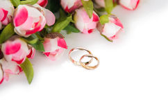 The wedding rings and flowers isolated on white background Royalty Free Stock Images