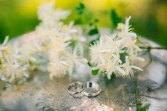 Wedding rings on the flowers of jasmine on a metallic silver tra. Y. Wedding jewelry Stock Photo