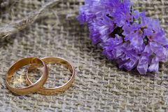 Wedding rings and flowers on a linen background Royalty Free Stock Image