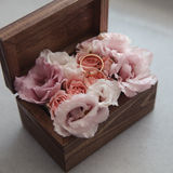 Wedding rings on flowers in old rustic wooden box for wedding ceremony Royalty Free Stock Images
