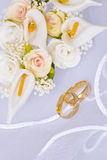 Wedding rings and flowers over veil. Wedding rings and flowers decorations over bridal veil Royalty Free Stock Image