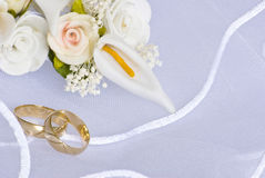 Wedding rings and flowers over veil. Wedding rings and flowers decorations over bridal veil Royalty Free Stock Photos