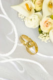 Wedding rings and flowers over veil. Wedding rings and flowers decorations over bridal veil Stock Photos