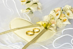Wedding rings and flowers over veil Stock Image