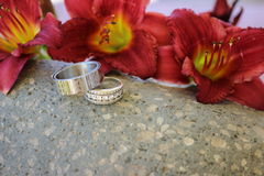 Wedding rings with flowers. Wedding rings resting on a rock with red Lilly's as a background Royalty Free Stock Image