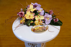 Wedding rings with flowers. Wedding rings on a saucer on the table with flowers Royalty Free Stock Images