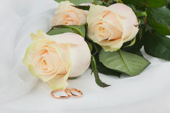 Wedding rings and flowers on silk Stock Photo