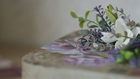 Wedding rings with flowers on a table. Wedding rings with flowers on table stock footage