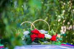 Wedding rings and flowers. In green branches Stock Photo