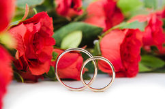 The wedding rings and flowers  on white background Stock Images