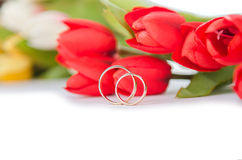 The wedding rings and flowers  on white background. Wedding rings and flowers  on white background Stock Photo