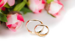 The wedding rings and flowers  on white background. Wedding rings and flowers  on white background Stock Photos