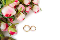 The wedding rings and flowers  on white background. Wedding rings and flowers  on white background Royalty Free Stock Image