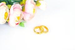 Wedding rings with flowers on white. Background Royalty Free Stock Photos