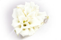 Wedding rings in front of a wedding bouquet Royalty Free Stock Image