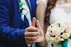 Wedding rings on funny thumbs stock images