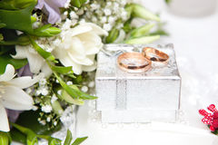 Wedding rings, gift box and flowers Royalty Free Stock Photography