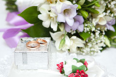 Wedding rings, gift box and flowers Royalty Free Stock Photos