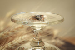 Wedding rings on a glass. - (Close up) stock images