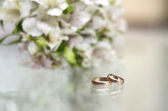 Wedding rings on a glass table. Gold wedding rings lie on a glass table next to the bouquet Stock Photo