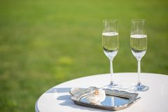 Wedding rings and glasses of champagne stock photo