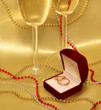 Wedding rings and glasses with sparkling wine on a golden background. A composition Valentine's Day: Satin drapery, decorated with beads, which is velvet red Stock Image
