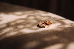 Wedding rings in gooms home. The sun rays fall on the rings stock photography