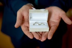 Wedding rings. Groom is holding weddings rings in his hands in white box Stock Photography