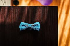Wedding rings on the groom`s butterfly on the wooden table royalty free stock photo
