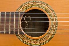 Wedding rings on guitar Stock Photos