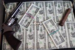 Wedding rings,gun, cigar and money in a case Stock Photos