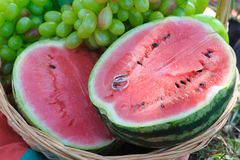 Wedding rings on half of a watermelon. Two wedding rings on half a watermelon. Beautiful juicy watermelon. Halves fresh watermelon, grapes, apple in a basket Stock Photography