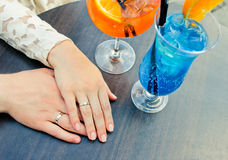 Wedding rings on hand bride and fiance. Colored cocktail. Stock Image