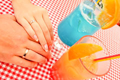 Wedding rings on hand bride and fiance. Colored cocktail. Royalty Free Stock Photo