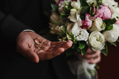 Wedding rings in the hand of the groom. And the bridal bouquet Royalty Free Stock Images