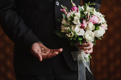 Wedding rings in the hand of the groom. And the bridal bouquet Stock Photography