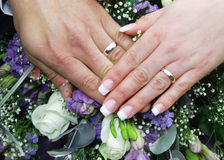 Wedding rings and hands 2. Wedding rings on bride and grooms hands on top of flowers Stock Photos