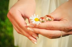 Wedding rings on hands of the bride on a camoline Royalty Free Stock Images