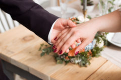 Wedding rings and hands of bride and groom. young wedding couple at ceremony. matrimony. man and woman in love. two happy people c Stock Images